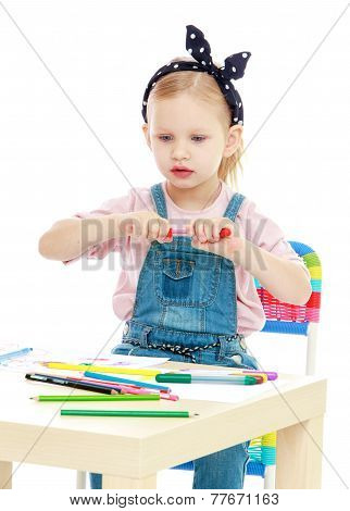 Charming little girl draws with markers while sitting at table.