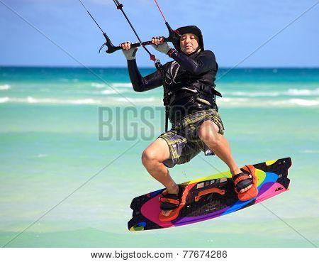 Man in a flight over water. Kitesurfing on the coast of Cuba.