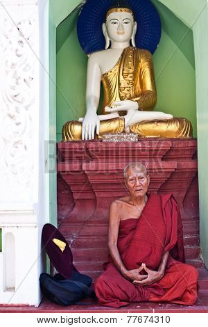 YANGON, MYANMAR - JANUARY 29 :Old buddhist monk sits by a shrine in the Shwedagon temple Jan 29, 2010, Myanmar.Shwedagon temple being the  most important  Buddhist site for the people of Myanmar.