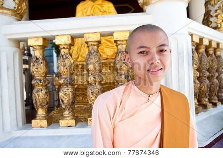 YANGON, MYANMAR - JANUARY 29 :A female buddhist nun sits in a shrine in the Shwedagon temple Jan 29, 2010, Myanmar. Shwedagon temple being the most important  Buddhist site for the people  of Myanmar.