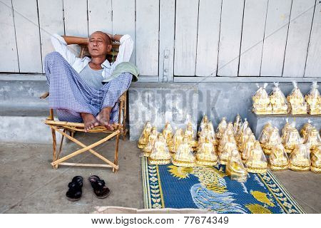 YANGON, MYANMAR - JANUARY 29 : Man snoozes at a shop of Buddhist souvenirs Jan 29, 2010, Myanmar. Small craft shops line the outter border of the Shwedagon Pagoda in central Yangon.