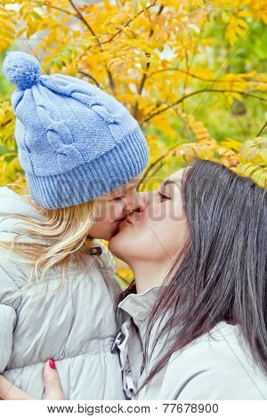 Mother And Daughter Kiss In Autumn