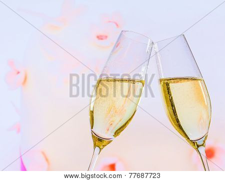 Champagne Flutes With Golden Bubbles On Wedding Cake Background