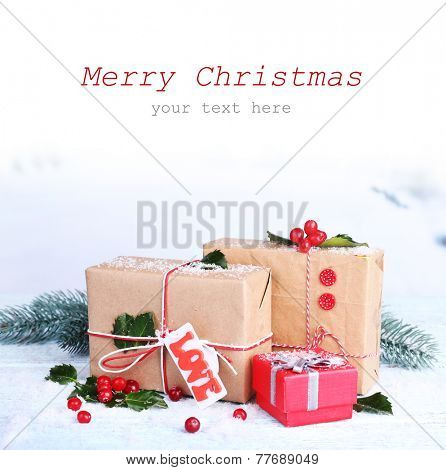 Beautiful Christmas gifts with European Holly (Ilex aquifolium) on light background