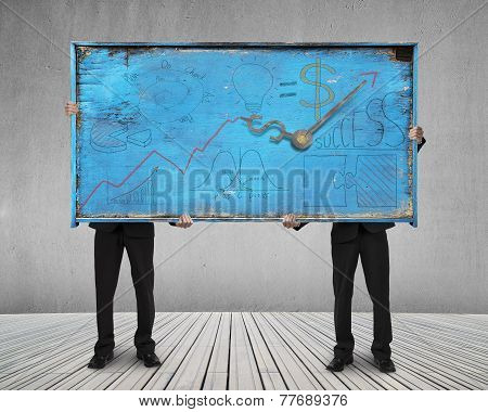 Two Men Holding Old Blue Doodles Billboard On Wooden Floor