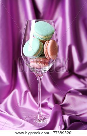 Gentle colorful macaroons in wine glass on color fabric background