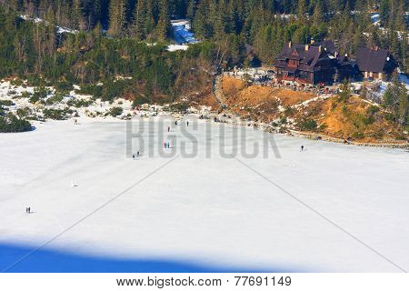 group of tourists are walking on the frozen Morskie Oko Lake