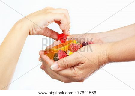 Child hand takes the candy from hands her mother close up