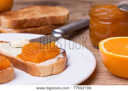 toasted slices of bread with butter and homemade orange jam on white plate.