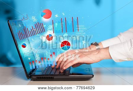 Hand typing on modern laptop notebook computer with future graph icons and symbols
