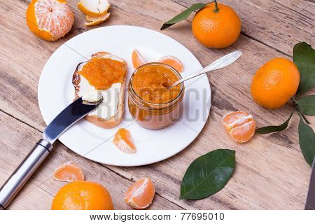 toasted slice of bread with butter and homemade tangerine jam on white plate.