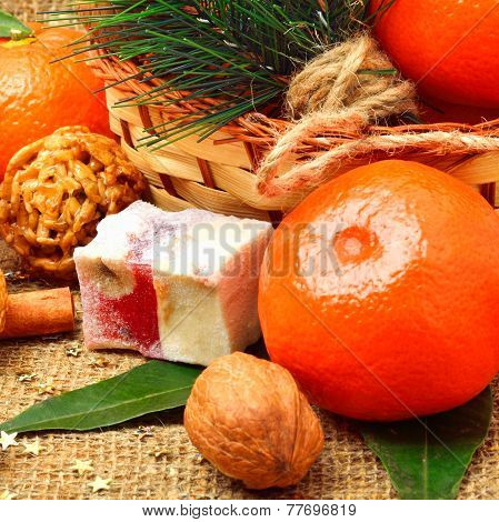 Christmas Tangerines With Sweet Delights, Walnuts, Pinecone And Brittle Candies On Christmas Sacking