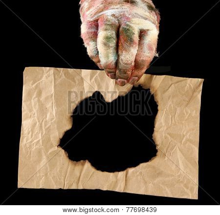 Hand of mummy holding old paper isolated on black