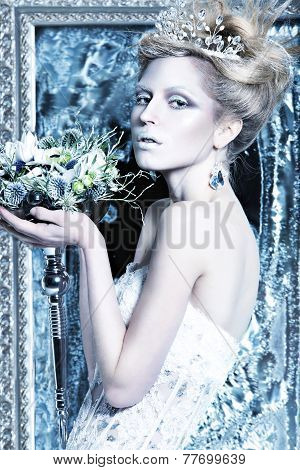 Beautiful girl in white dress in the image of the Snow Queen with a crown on her head.