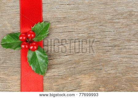 European Holly (Ilex aquifolium) with berries on wooden background