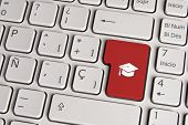 stock photo of graduation hat  - Spanish keyboard with education graduation hat icon over red background button - JPG