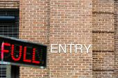 picture of front-entry  - Entry sign to parking lot on brick wall with lighted Full sign out front - JPG