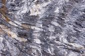 foto of gneiss  - Close up of rock surface gneiss with white folded quartz veins due to the power of geologic crustal movement - JPG