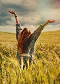 picture of breathtaking  - fashion young red hair woman standing back hands up on breathtaking view of dramatic storm sky in the field - JPG