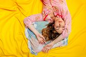 stock photo of sleeping  - girl in pajamas sleeping on the yellow sheet - JPG