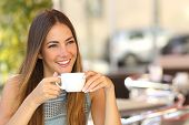 stock photo of adolescence  - Happy pensive woman thinking in a coffee shop terrace in the street - JPG