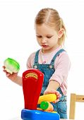 stock photo of montessori school  - Little girl hanging in the balance fruit  - JPG