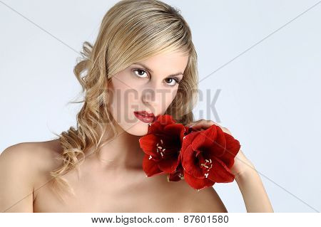 beautiful blond girl with red amaryllis flower on a white background
