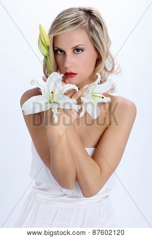 beautiful blond girl with white lily flower on a white backgroun