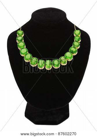 Pendant With Green Gem Stones On Black Mannequin Isolated On White