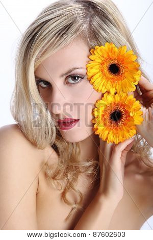 beautiful blond girl with gerber daisy flower on a white background