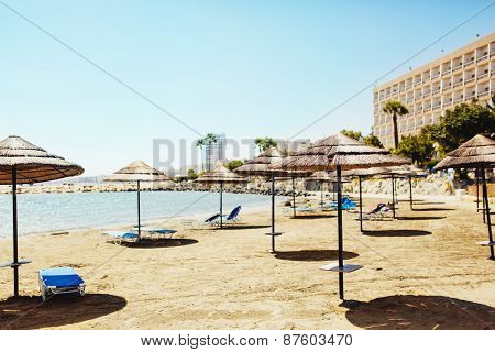 Sunshade Umbrellas with lounge chairs on the beach at hot summer day