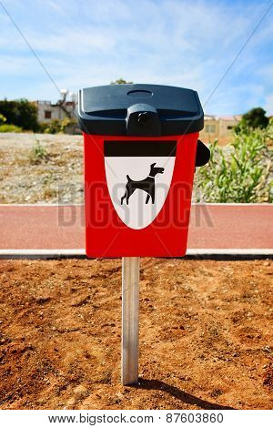 Red dog waste container in a park