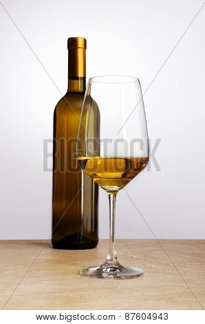 bottle of white wine with glass flat on the table