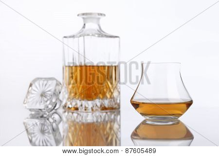 bottle and glass of brandy on a white background