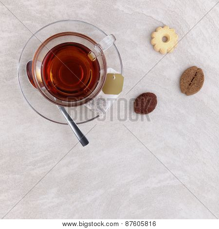 Glass cup of tea with cookies on the table