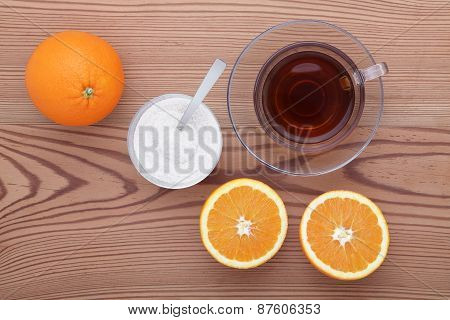 Glass cup of tea with sugar and orange on the table