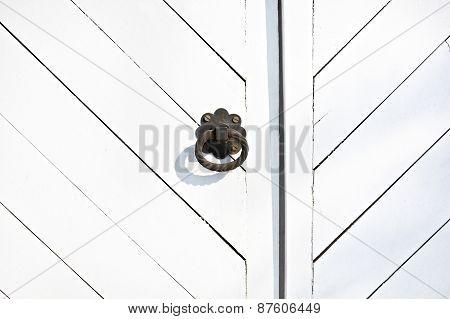 Black metal door knob (handle) on the white wooden door