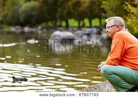 Profile of aged man in glasses sitting near pond in park watching ducks