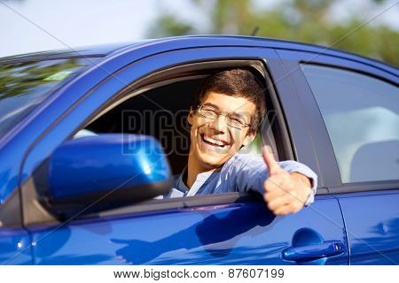 Smiling handsome young driver showing thumb up through open car window