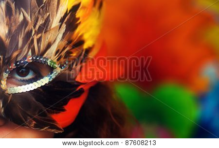 Young Woman With A Colorful Feather Carnival Face Mask On Bright Colorful Background, Eye Contact, M