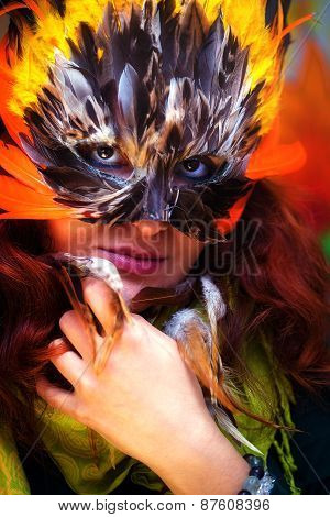 Young Woman With A Colorful Feather Carnival Face Mask Eye Contact