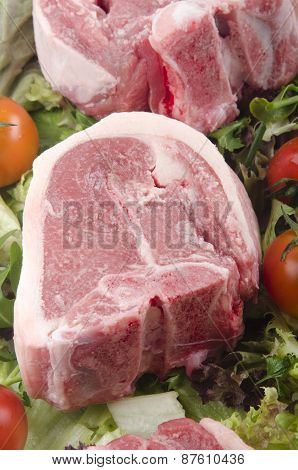 Raw Lamb Chops With Tomato On Fresh Salad