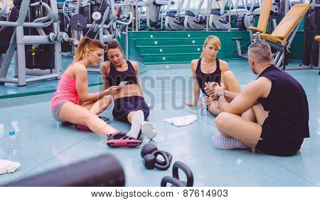Women looking smartphone and couple friends talking in the gym