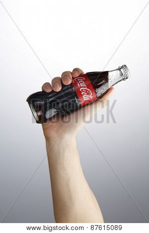 Kuala Lumpur,Malaysia 9th April 2015,Photo of a hand holding glass bottle of Coca Cola - Refreshing. Wet with water ice droplets