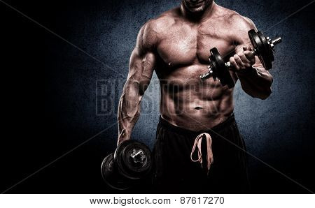 Closeup Of A Muscular Young Man Lifting Weights On Dark Background