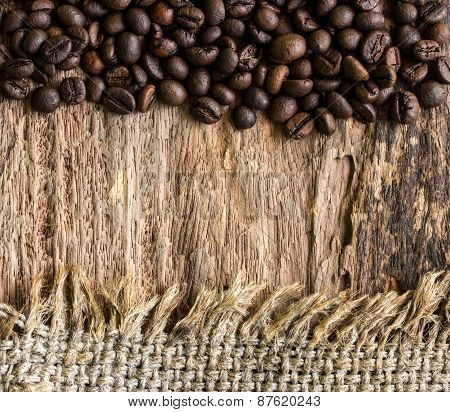 Coffee Beans And Hemp Sack On Wooden Background.