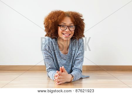 Black African American Teenage Girl Lying Down On The Wood Floor