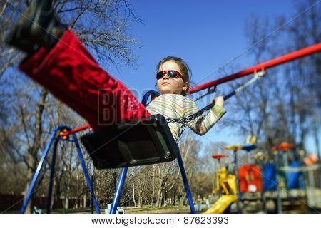 Cute Little Girl Swinging Seesaw On Children Playground