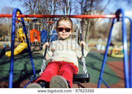 Cute Little Girl Swinging Seesaw On Children Playground
