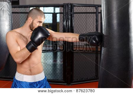 Sportsmen kicking punching bag